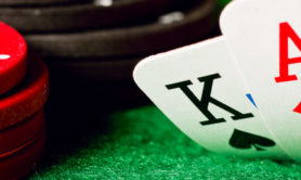 Gambling chips, ace of diamonds and king of spades on green poker cloth.