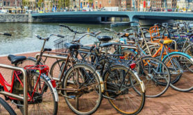 Row of Bicycles parked next to Amsterdam City Center (Centrum). Visible are typical Church and Dutch Houses in the background. Amsterdam, The Netherlands.