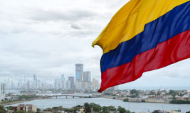 Colombian flag waving on the wind and modern Cartagena district behind it
