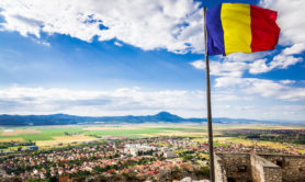 Romanian flag flying above the town of Rasnov, Transylvania, Romania. The flag flies against a bright blue sky and cloudscape, with the rural town of Rasnov spread out below, with the mountains at the horizon beyond. The flag is located at the top of the famous citadel in Rasnov. Horizontal colour image.