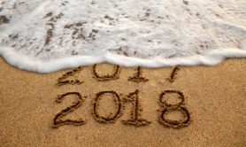 New year 2018 and old year 2017 written on sandy beach with waves