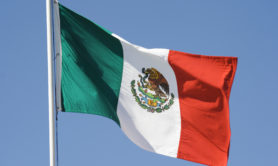 Horizontal view of a Mexican national flag waving in the wind against a clear blue sky.
